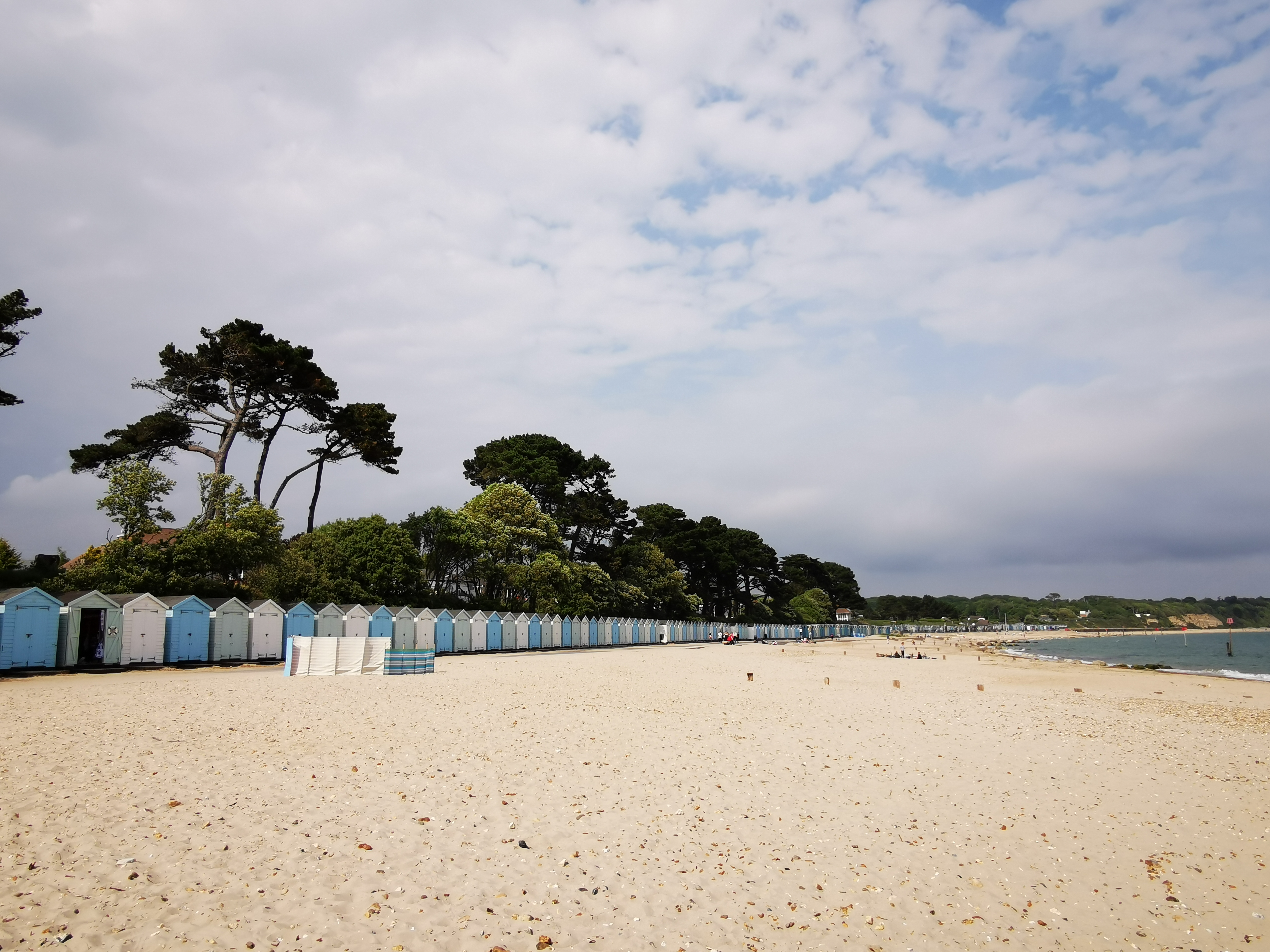 Shot looking down avon beach with the beach huts all lined up and beach goers enjoying the sun